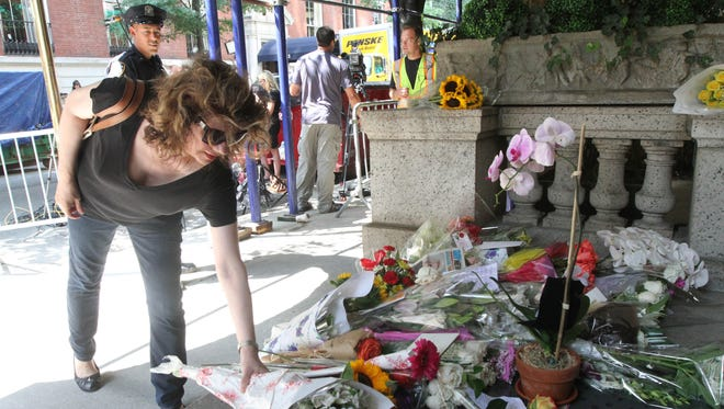 Paula Reardon places flowers at a sidewalk memorial for comedian Joan Rivers at the doorstep of her apartment building, Friday, Sept. 5, 2014 in New York. Rivers died Thursday at a New York hospital following complications from surgery. She was 81.  (AP Photo/Tina Fineberg)