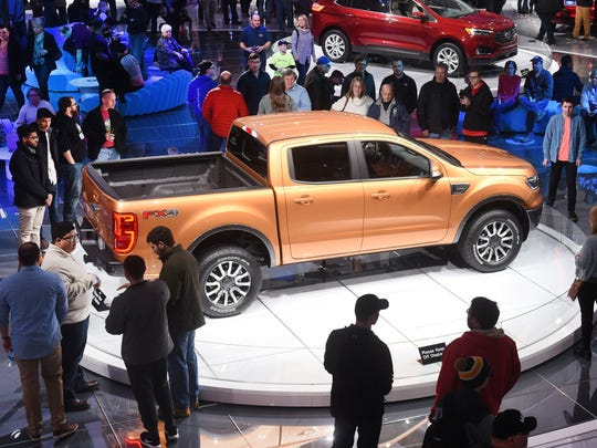 People look at the 2019 Ford Ranger pickup on display at Cobo Center January 20, 2018, during the first public day of the North American International Auto Show.