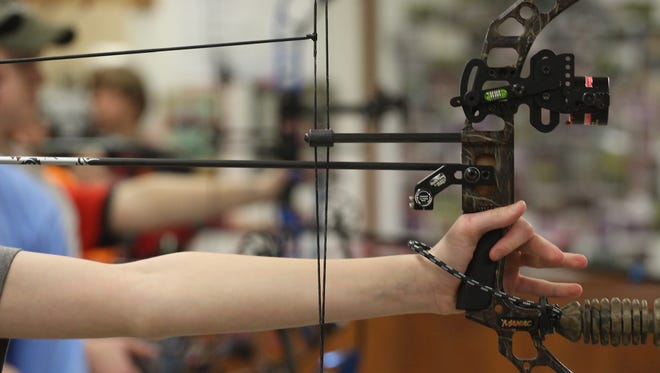 An archer holds her bow after firing at the Rib Mountain Bowmen archery club during Badger State Games competition, Saturday, January 24, 2015, in the town of Maine, north of Wausau.