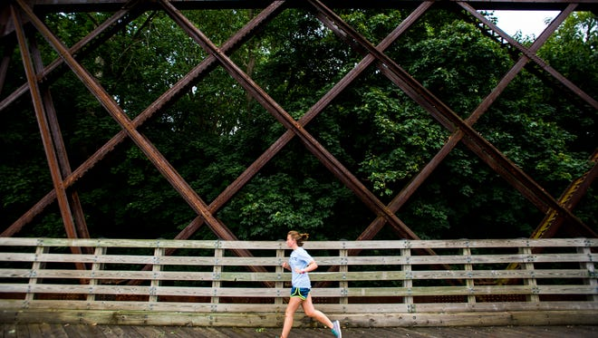 Emily Hockley of Lebanon runs across the historic iron bridge on the Lebanon Valley Rail Trail in Cornwall on Monday, August 10, 2015. Despite a dreary day people were still out and about on the rail trail.