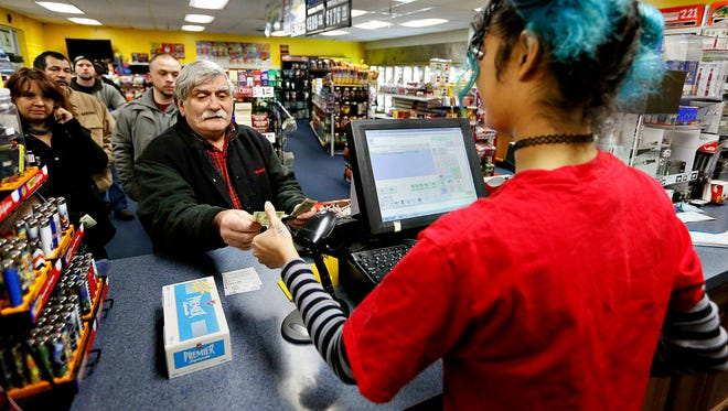 Sara Zaidi, right, of Cocoa Hut Convenience Store on East Market Street, sells Powerball tickets to Donald Smith, left, of Hellam,  as a line forms behind him at the store in York, Pa. on Saturday, Jan. 9, 2016. (Dawn J. Sagert - The York Dispatch)