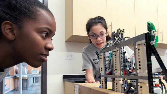 York Country Day sixth-graders Jadaiya Mitchell, left, and Caroline Danner keep an eye on a robot's movements as the students practiced with the EV3 Lego robot at the school Thursday, May 4, 2017. Their team, the Cyber Hounds, will be competing in the First Lego League International Open Championship in Bath, England in June. Bill Kalina photo