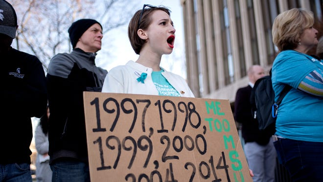 Nassar survivor Morgan McCaul cheers during the Rally for Resignations on Friday, April 20, 2018, in front of the Hannah Administration Building on the Michigan State University campus in East Lansing. Students protested alongside survivors of Larry Nassar and their families.