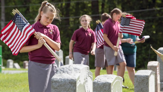 Sarah Perry, left, prepares to place an American flag on a grave site of a military veteran. Some 40 students from St. Rose of Lima Elementary School in Jackson Township placed about 700 flags at Holy Savior Cemetery in Manchester Township this week to prepare the cemetery for Memorial Day.