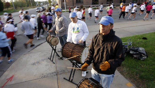 Members of the group Tubabu (left to right) Dan Kopatich, Bob Miller and Michael Thompson play a beat as Des Moines Marathon runners turn onto Court Avenue in 2008.