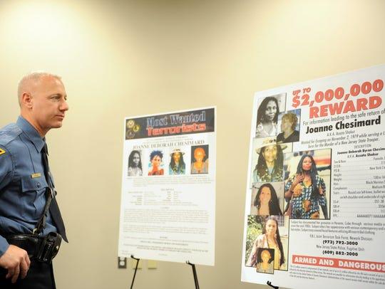 A New Jersey State Trooper looks over a reward billboard