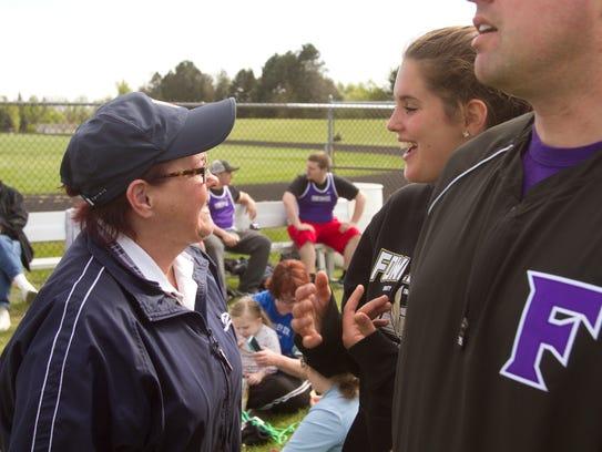 Debi (Hughes) Douglass, left, holds Fowlerville track