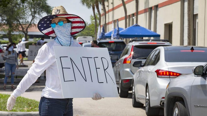 "Casey Haltigan directs traffic at SA Co., a Boca-based firm. The company is distributing 100,000 free ""Face Shield"" tubular bandanas to residents, who are being asked to wear face coverings in public. Traffic backed up for more than a mile in several directions in Boca Raton, Wednesday, April 15, 2020."
