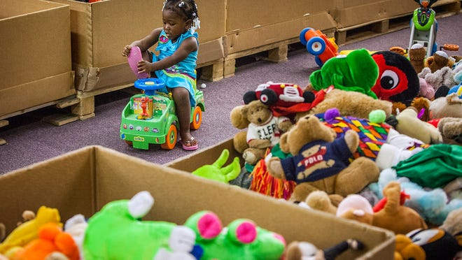 Marsheala Stewart, 2, tries out a toy truck at Buy the Pound Thursday morning.