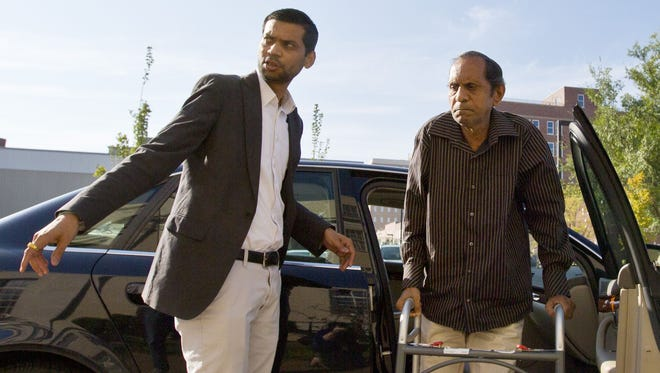 Chirag Patel helps his father, Sureshbhai Patel, out of the car as they arrive outside the federal courthouse before start of a trial against Madison, Ala., police Officer Eric Sloan Parker, Tuesday, Sept. 1, 2015, in Huntsville, Ala. Sureshbhai Patel, who was visiting relatives from his native India in February, was walking in his son's neighborhood when police responding to a call about a suspicious person stopped to question him. A police video captured an officer slamming the man to the ground, partially paralyzing him. (AP Photo/Brynn Anderson)