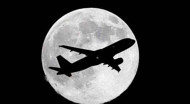 "One day before a ""supermoon,"" a commercial airliner crosses the waxing gibbous moon on its final approach to Los Angeles Airport as viewed from Whittier, Calif., on July 11, 2014."