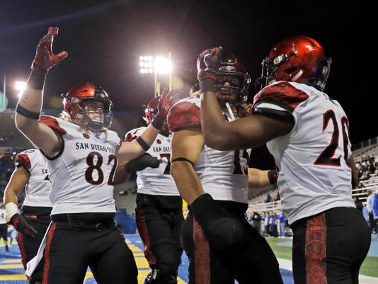 San Diego State running back Rashaad Penny, right, is greeted by teammates in the end zone after his touchdown against San Jose State during the first half of an NCAA college football game Saturday, Nov. 4, 2017, in San Jose, Calif. (AP Photo/Marcio Jose Sanchez)