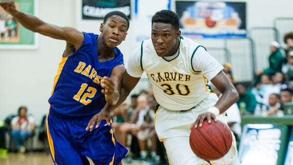 Carver's Keondre Davis (30) drives against Daphne's Dre Graves (12) in subregional action at Carver High School in Montgomery, Ala. on Tuesday February 16, 2016.