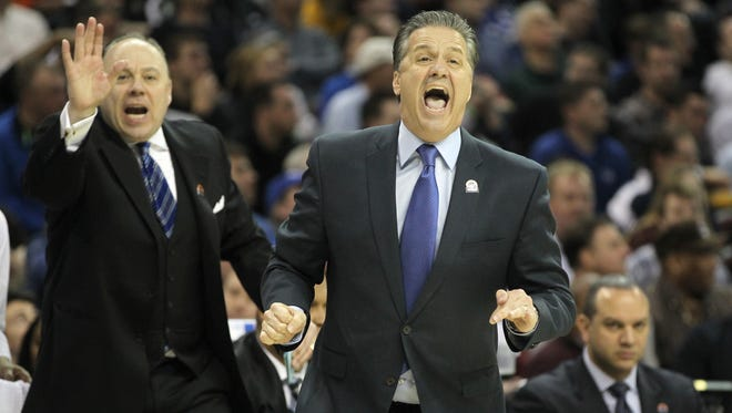 Kentucky Wildcats head coach John Caliper, center, and assistant coach Barry Rohrssen react to a call during the first half of an NCAA tournament college basketball game in the Round of 16, Thursday, March 26, 2015, at Quicken Loans Arena in Cleveland.