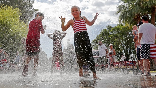 Kids play in water sprayed by the Phoenix Fire Department during the Arcadia 4th of July parade in Phoenix on July 4, 2018. This is the 23 year of the community event.