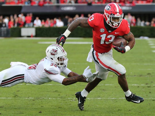 Georgia tailback Elijah Holyfield breaks away from Massachusetts safety Tyler Hayes for a touchdown during the first half of an NCAA college football game, Saturday, Nov. 17, 2018, in Athens, Ga. (Curtis Compton/Atlanta Journal-Constitution via AP)