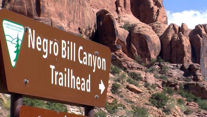 FILE - This undated photo shows a sign at the entrance of the Negro Bill Canyon Trailhead in Moab, Utah. The renewed national scrutiny of the Confederate flag has officials again considering changing the name of Utah's Negro Bill Canyon, though the title that some find offensive is a point of historical pride for others.