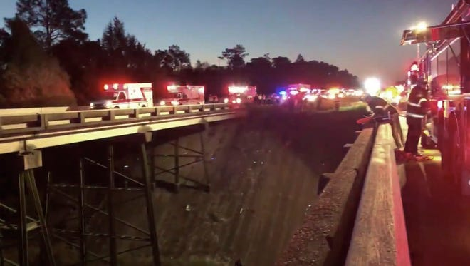 This photo provided by Jesus Tejada shows first responders looking down at a bus that plunged into a ravine, Tuesday, March 13, 2018 on Interstate 10,  Loxley, Ala. Several people were on board, and all of them were brought to 10 hospitals in Alabama and Florida, either by helicopter or ambulance, said Baldwin County Sheriff Huey Hoss Mack.