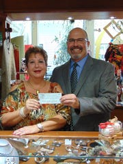 "Sofia Valente Mateus, owner of So Unique Gallery Boutique, presenting Bill West, CEO of Molly's House, a check for more than $1,600 that was raised at the ""Sip, Shop & Shine"" event benefiting Molly's House."