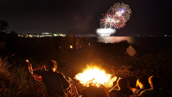 People watch the Fourth of July fireworks near small fires on the beach Saturday July 4, 2015 in Sheboygan near King Park.