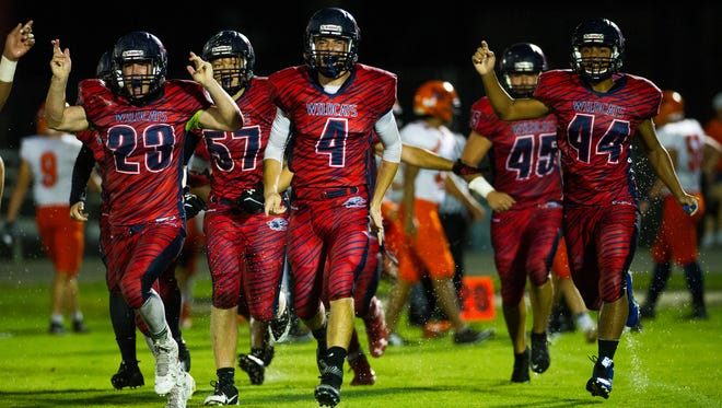 Estero High School's football team celebrates a big play during a game against Lemon Bay in Estero, Fla., on Friday, Sept. 2, 2016.