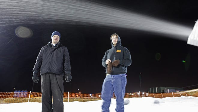Ryan Suhr (left) and Jeff Kirby monitor the snowmaking machine.