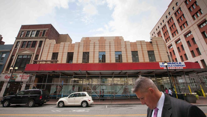 Scaffolding surrounds an apartment project being built atop a Walgreen store on Market Street in Wilmington. Business owners are hopeful a flood of new residential projects will help revive the area.