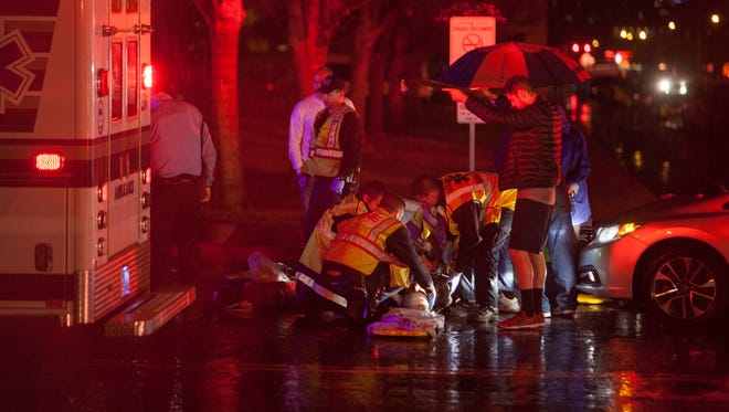 Paramedics respond to two pedestrians after they were struck by a car near Dixie State University Tuesday, Jan. 5, 2016.