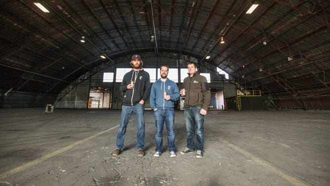(From left:) MadTree co-founders Brady Duncan, Kenny McNutt and Jeff Hunt stand in the hangar of the former RockTenn paper manufacturing facility at 3301 Madison Ave. It will serve as the new location of MadTree Brewing Co.