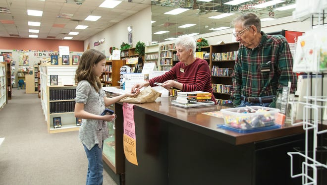 Volunteers Don and Florence Molsberry assist Nicole Telles during her visit to Books Revisited.