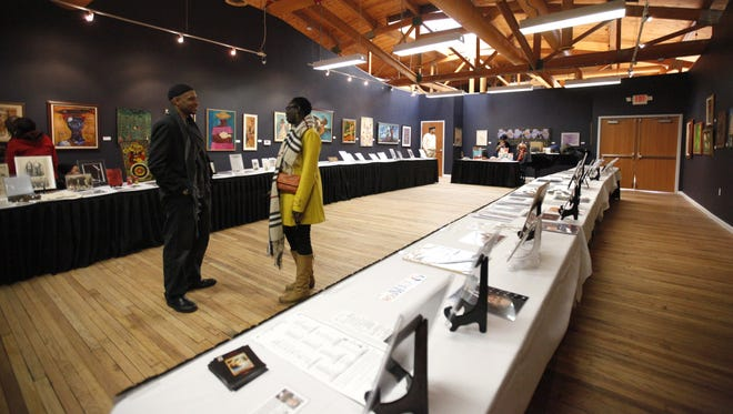 """Khalid el-Hakim of Detroit, founder and CEO of the Black History 101 Mobile Museum, speaks with a guest of his """"Drum Majors for Justice"""" exhibit at the N'Namdi Gallery in Detroit in 2012. The gallery is part of Detroit's Sugar Hill Arts District."""