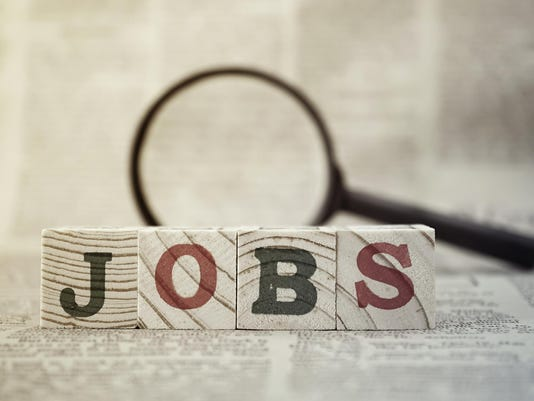 """""""Jobs"""" on wooden block and magnifying glass on newspaper background"""
