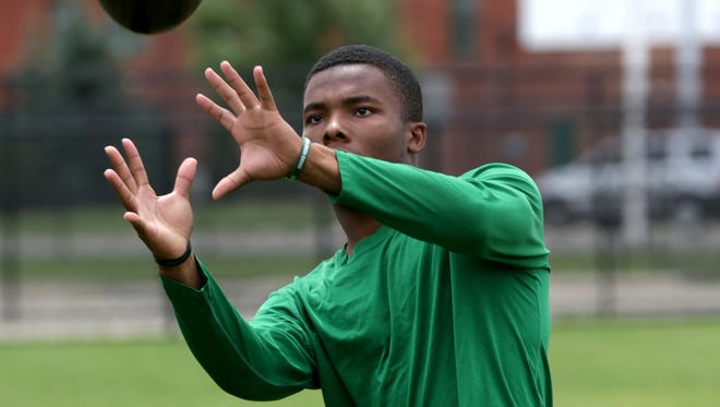 Kalon Gervin plays catch during a light practice on the football field at Cass Technical High School in Detroit on Aug. 18.