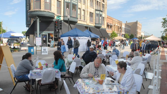 """People eat pie in the street at the """"Pie on the Porch"""" during the Oshkosh Farmer's Market in 2013."""