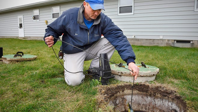 Ben Pfluege, Watab Inc., lowers a camera into a septic tank to check the baffles during an inspection and certification of a system Thursday, Nov. 5 at a home for sale near Opole. Currently Stearns County requires proof that a septic system is working properly before finalizing the sale of property.