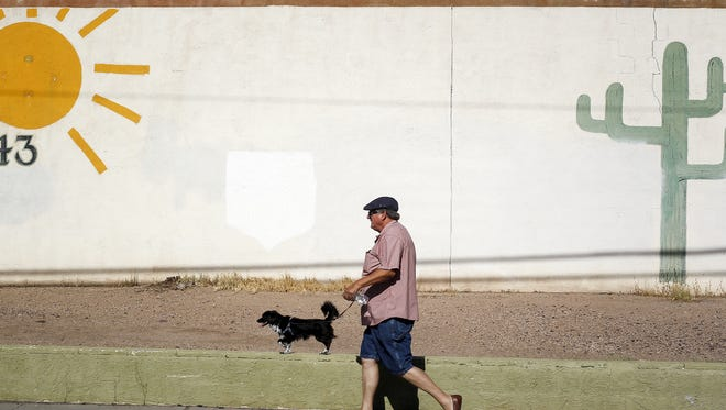 Michael Potocnik from Phoenix walks his dog along 7th St. and Whitton Ave. on July 12, 2016