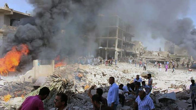 In this photo released by the Syrian official news agency SANA, Syrians gather at the scene where twin bombings struck Kurdish town of Qamishli, Syria, Wednesday, July 27, 2016. Twin bombings struck a crowd in a predominantly Kurdish town in northern Syria on Wednesday, killing 44 people and wounding dozens more, Syria's state-run news agency and Kurdish media reported.