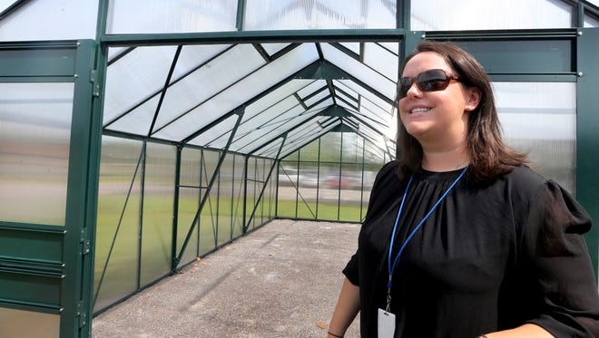 Meri-Leigh Smith, the Coordinator for School Health, talks about the farming program at Cason Lane Academy as she stands next to the school's new greenhouse, on Wednesday, Aug. 24, 2016.