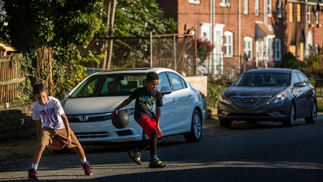 Jorge Diaz, 10, (left) and Nyair Matthews, 11, play  on Monday play on the Canby Park Estates block where two Wilmington firefighters died in a September fire. The burnt-out shell for residents is a stark reminder of changes in the close-knit neighborhood.