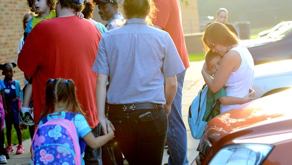A mother hugs her son as they wait outside school on