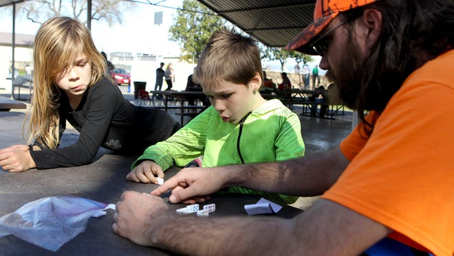 John Roberts, right, plays games with his kids Dakota, 10 , and Kairi, 9, Tuesday at the Silver Dollar Fairgrounds in Chico. They along with his wife, Jennifer, and other son Liam, 3, were at the shelter after they were evacuated from their Marysville home.