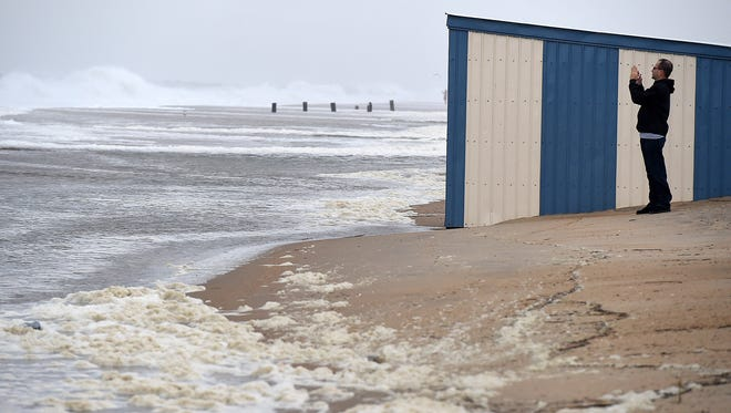 A passerby takes pictures of the waves from Hurricane Jose pounding Rehoboth Beach.
