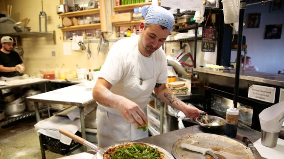 Chef Manny Augello dresses a Runaway with black truffle rubbed arugula to serve at Bread and Circus Provisions' pizza pop-up night in Lafayette May 4, 2016.