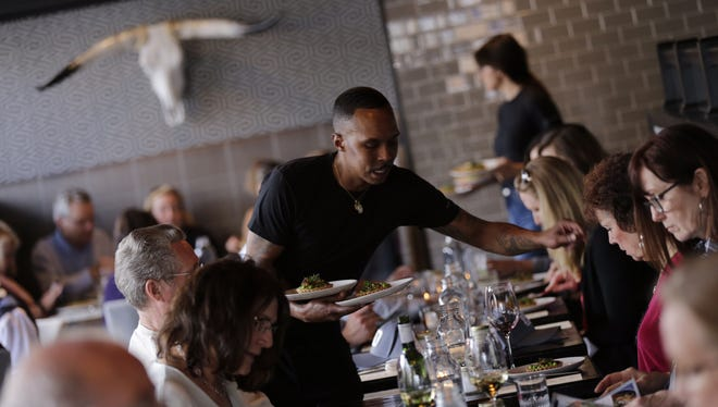 Server Edward Dotson delivers food to a table at Grey Ghost, the first restaurant to be spotlighted in the 2017 Detroit Free Press Metro Detroit Chevy Dealers Top 10 Takeover dining series event Tuesday, April 11, 2017.