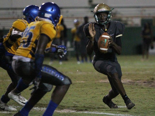 Lincoln's Chris Beard rolls out to throw a pass during Friday's spring jamboree between Godby, Lincoln and Rickards at Florida A&M's Bragg Memorial Stadium.
