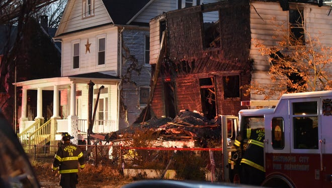 Baltimore City firefighters remain on the scene early Thursday, Jan. 12, 2017, after a fire on Springwood Avenue in northeast Baltimore. Several children and an adult were taken to an area hospital. Six children are still missing.