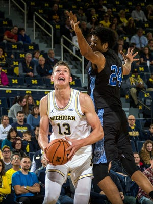 Michigan's Moe Wagner handles the ball under the basket as Grand Valley State's Justin Greason defends in the first half of an exhibition Friday, Nov. 3, 2017 at Crisler Center in Ann Arbor.