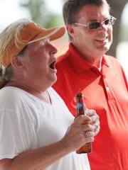 Lauren Divet, left, reacts after finding out her husband Jeff, right, won a house which was the grand prize during a miniature golf tournament held by Fucillo Kia at Mike Greenwell's on Thursday.