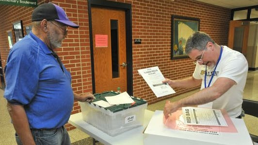 Election center worker Mark DiCorcia (right) checks the contents of election materials from a polling place brought in by Henry Jones to the regional election center at IPS School 15 on May 8, 2012.