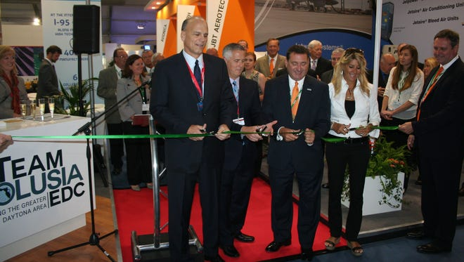 Gary Spulak, left, Chris Appleton, both of Embraer, Gray Swoope of Enterprise Florida Inc., and Carol Craig of Craig Technologies at a ribbon-cutting.